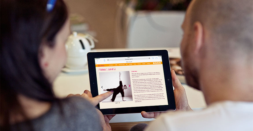 A couple reviewing a yoga center's class on a tablet responsive design localized for a better user experience.